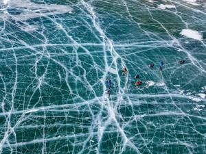 اسکیت بازها روی دریاچه یخ زده بایکل، روسیه دریاچه بایکال هرساله یخ می زند و بزرگترین یخ درجهان است که با ترک های کوچک و زیاد شبیه به تار عنکبوت می شود. عکاس: Evgeny Dubinchuk
